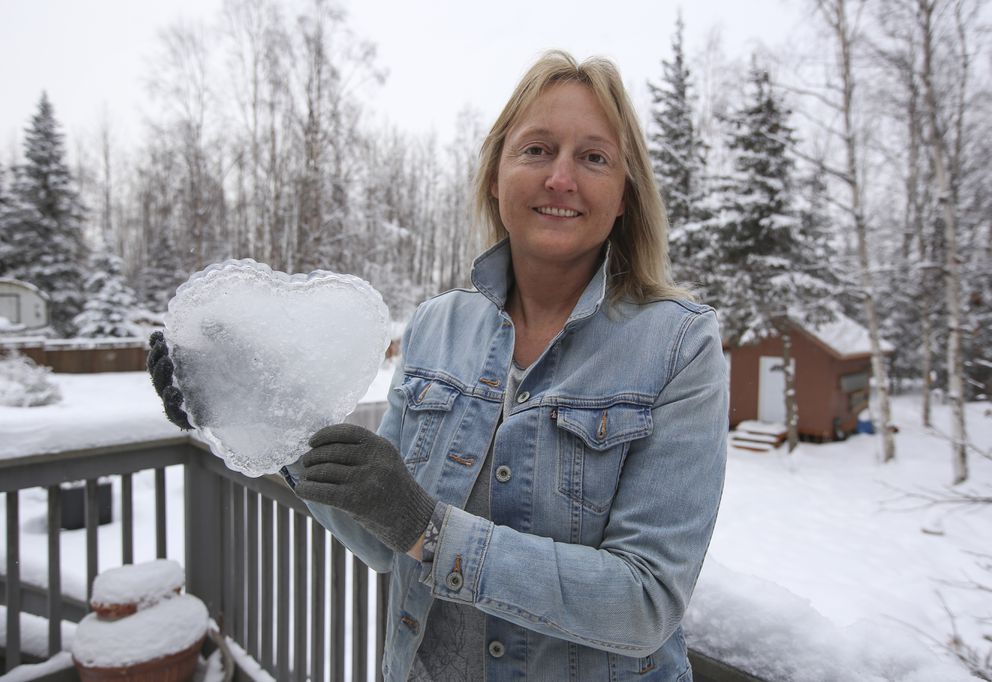 Chantelle Pence holds a piece of ice she made into the shape of a heart outside her home in Anchorage on Tuesday. (Emily Mesner / ADN)