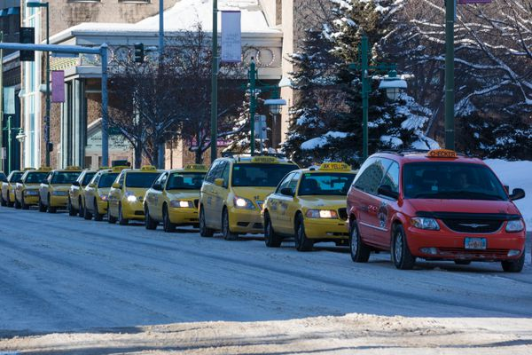 Taxi drivers stage a rolling strike past city hall on Friday, Feb. 23, 2018. The Anchorage Taxi Workers Alliance wants to see the city regulate ride hailing services like Uber and Lyft and pause the issuance of new taxi permits, among other demands. (Loren Holmes / ADN)