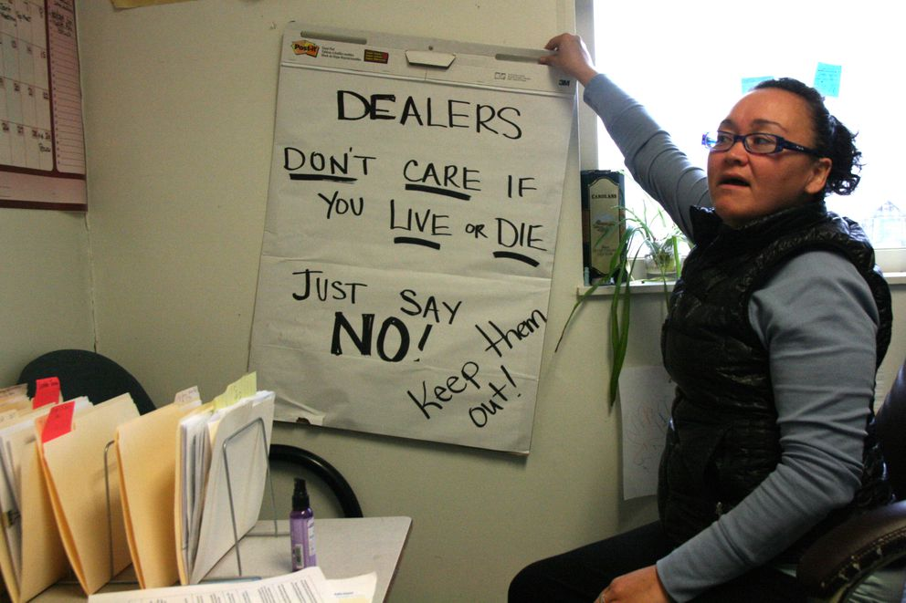 "Michelle ""Misty"" Matthew, city administrator in Quinhagak, in her office on Sept. 15, 2016, shows a sign that she used in a rally to protest drug dealing after four heroin overdoses including one death in the Southwest Alaska village. (Lisa Demer / Alaska Dispatch News)"