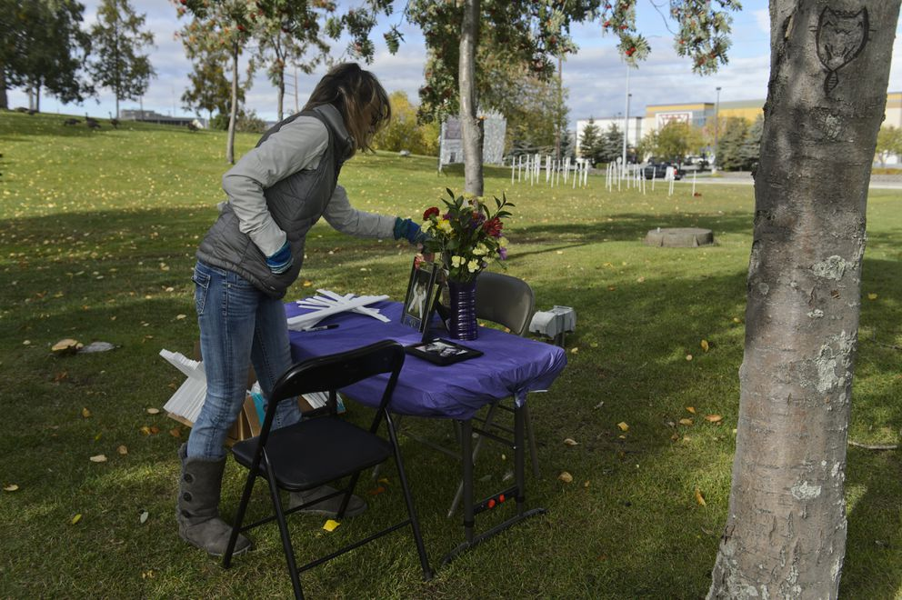 Karen Malcolm-Smith, organizer of the Connection Overcomes Addiction event in Anchorage, sets a picture of her son at a cross signing station on September 18, 2020. Visitors have the opportunity to write the name of a person lost to addition on a cross and add it to the memorial display. (Marc Lester / ADN)