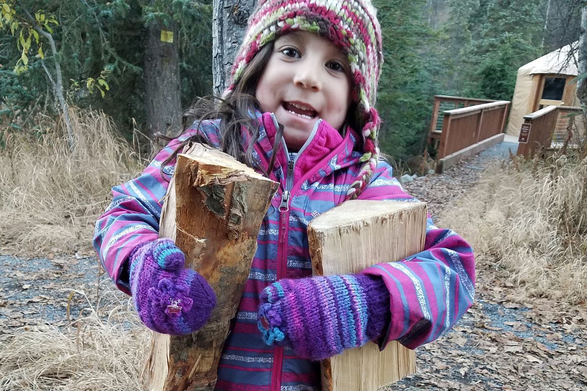 Lillianna Garcia, 5, carries wood during a lesson in safe fire-building during a late-fall overnight campout at Manitoba Cabin near Summit Lake. (Erin Kirkland)