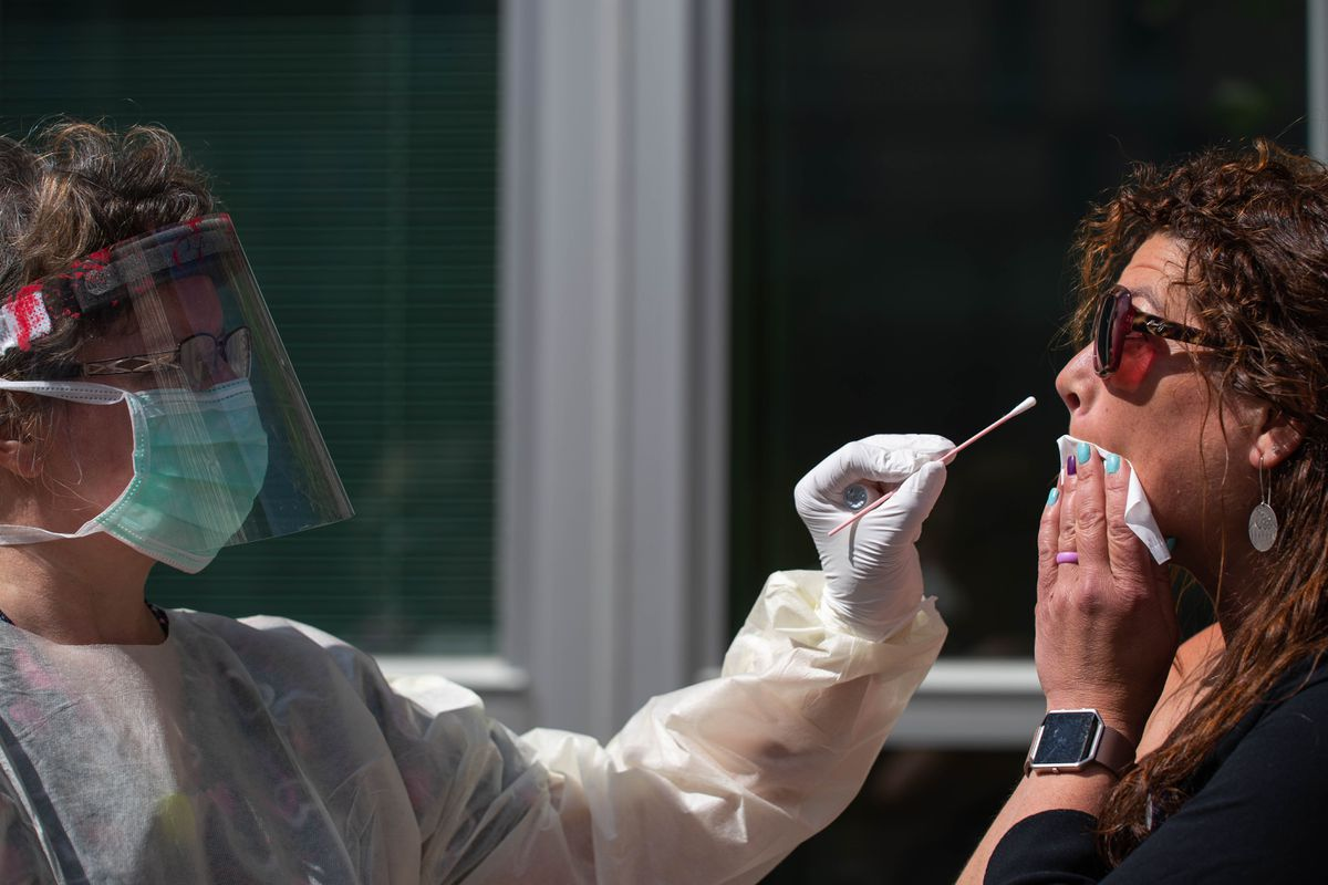 Valerie Murphy takes a nasal swab sample from Shirley Young at the Alaska Native Medical Center's COVID-19 walk-up testing site on Thursday, June 4, 2020. (Loren Holmes / ADN archive)