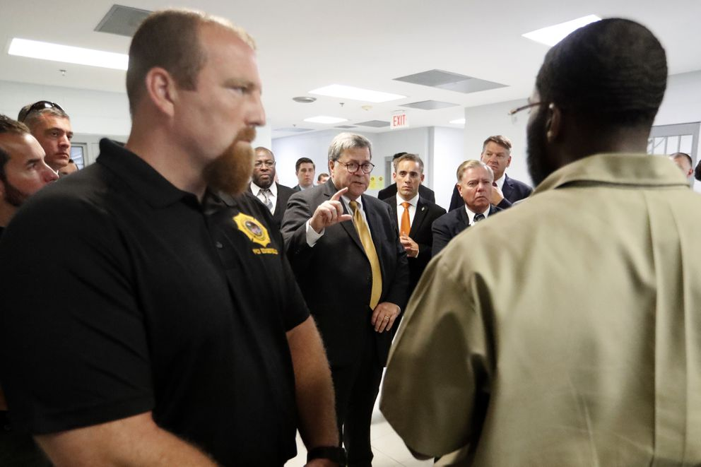 Attorney General William Barr, center, speaks to an inmate as he tours the Edgefield Federal Correctional Institution Monday, July 8, 2019, in Edgefiled, S.C. (AP Photo/John Bazemore)
