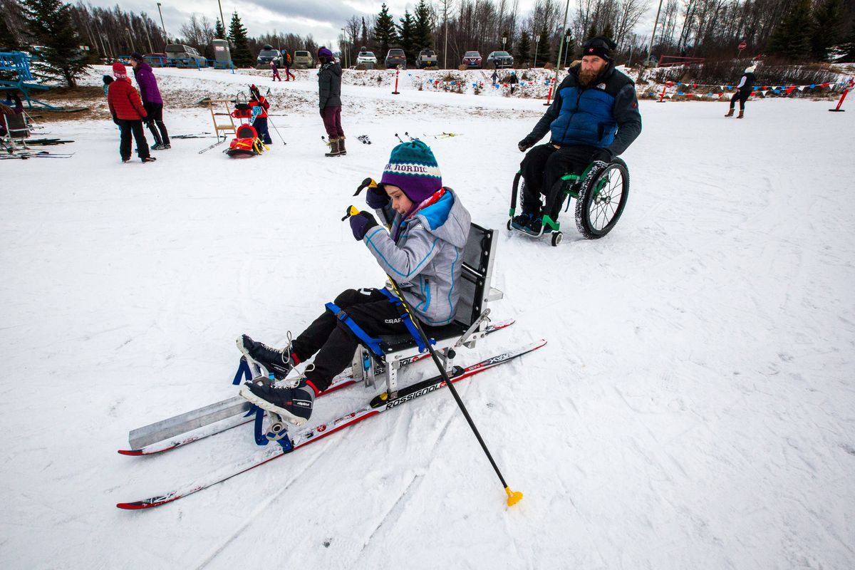 "Ira Edwards assists Scout Gramse, 8, as she slides on the snow on a nordic sit-ski on March 5, 2016, at Ski 4 Kids. By showing able-bodied youth adaptive gear, Edwards hopes to create understanding and appreciation for disabled athletes. Edwards' community outreach program ""Team Gimp Squad"" has donated eight nordic sit-skis to the Anchorage School District."