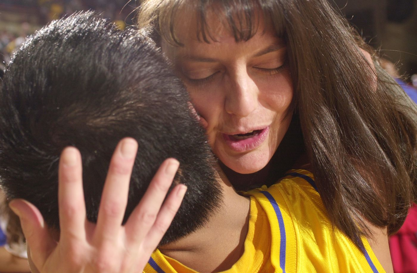 Kodiak head coach Amy (Rakers) Fogle hugs senior guard Geoffery Agmata after Kodiak's victory over East High at Sullivan Arena, giving them the state 4A championship, on March 24, 2001. (Marc Lester / ADN)