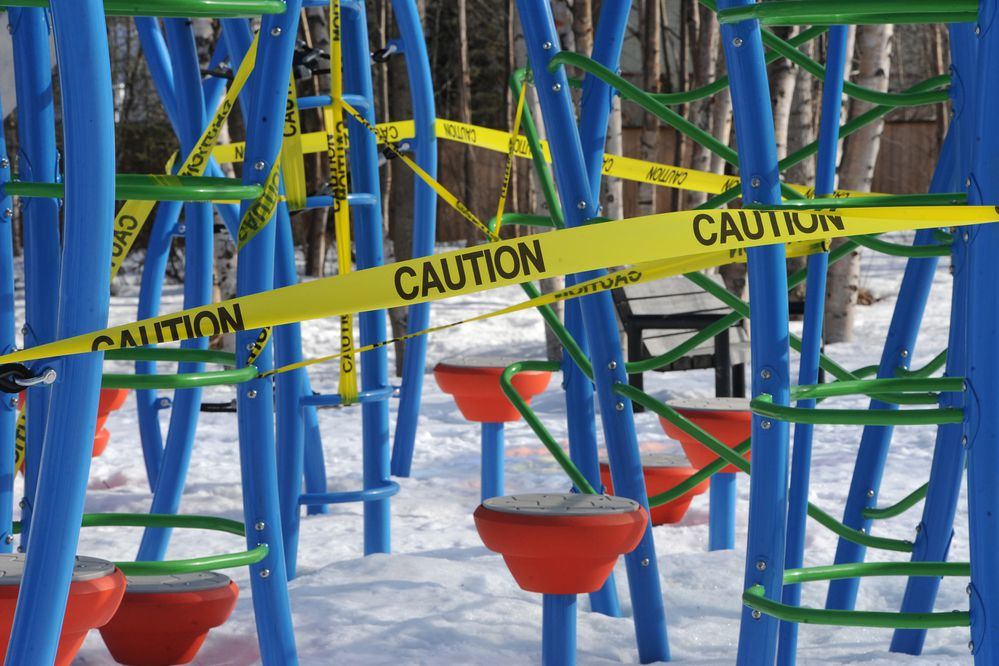 Playground equipment at city parks have been wrapped with caution tape to help prevent the spread of the coronavirus. Sunshine illuminates caution tape at Chugach Foothills Park on Sunday, April 5, 2020. (Bill Roth / ADN)