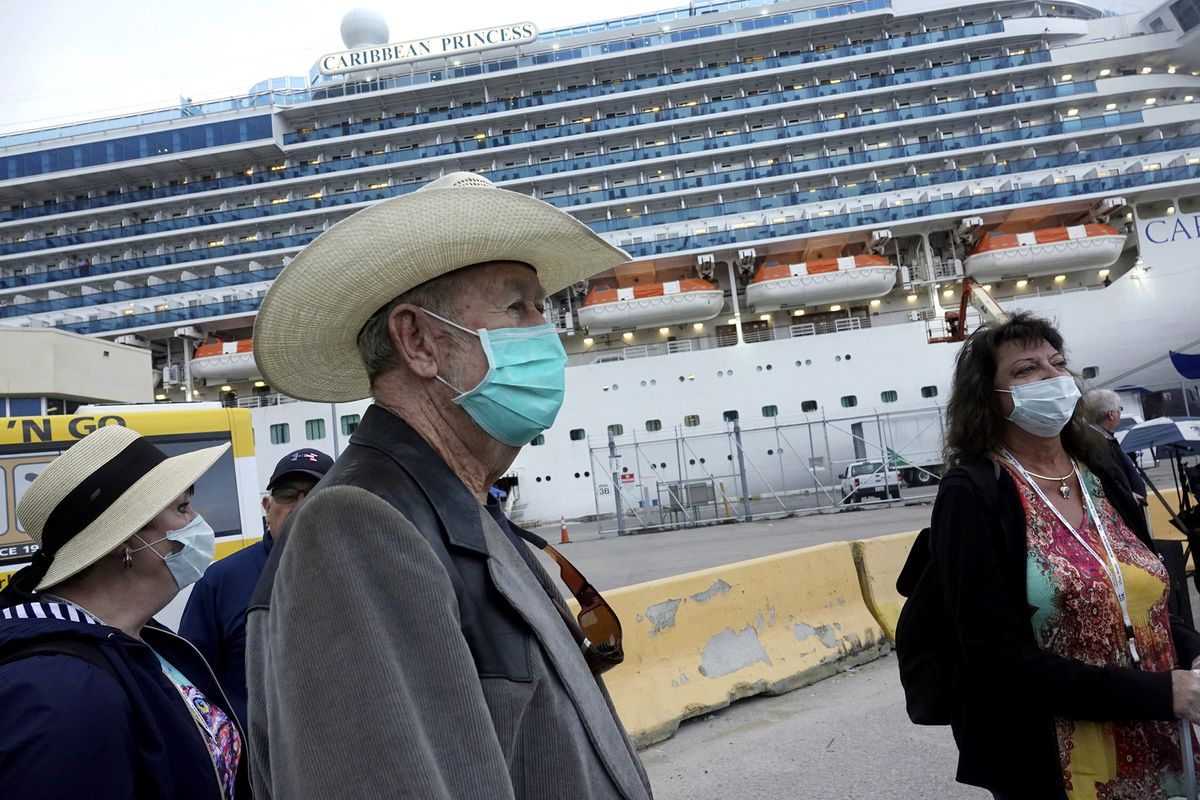 """Jana Harrelson, left, Ronny Young, and Karla Weston, right, all of Port St. Joe, Florida, disembark from the Caribbean Princess at Port Everglades in Fort Lauderdale, Fla., Wednesday, March 11, 2020. The cruise ship was been given federal permission to dock in Florida after testing of two crew members cleared them of the new coronavirus and U.S. health officials lifted a """"no sail"""