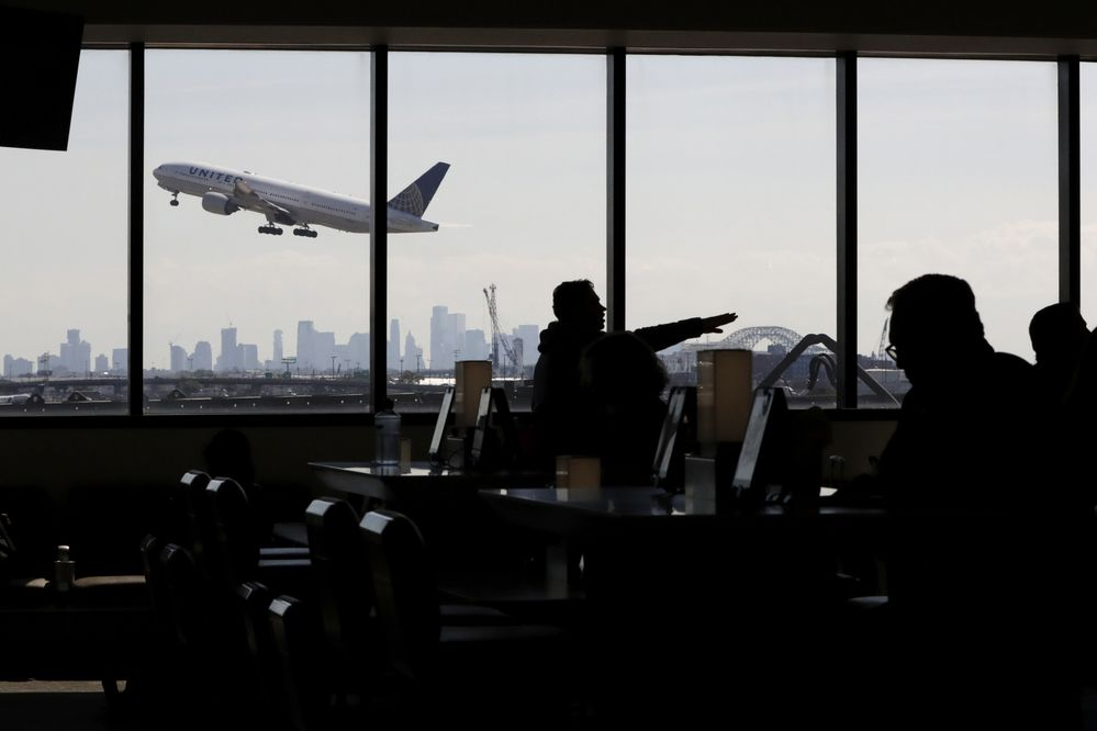 FILE - In this July 18, 2018, file photo, a United Airlines commercial jet takes off as travelers sit at a gate in Terminal C of Newark Liberty International Airport in Newark, N.J. Airlines are bowing to the staying power of higher fuel prices by culling unprofitable flights while trying to boost revenue by being nicer to customers. (AP Photo/Julio Cortez, File)