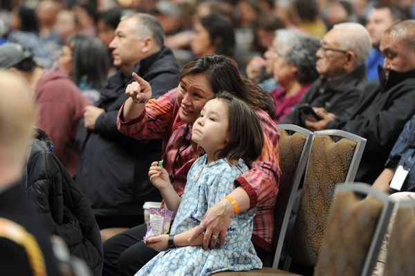 Melanie Bahnke, president of Kawerak Inc., a regional non-profit corporation in the Bering Straits Region, and Ivy Bahnke, 6, watch a slideshow during Gov. Bill Walker's speech on the first day of AFN Convention at the Dena'ina Center in Anchorage on Thursday, Oct. 19, 2017. (Bill Roth / Alaska Dispatch News)