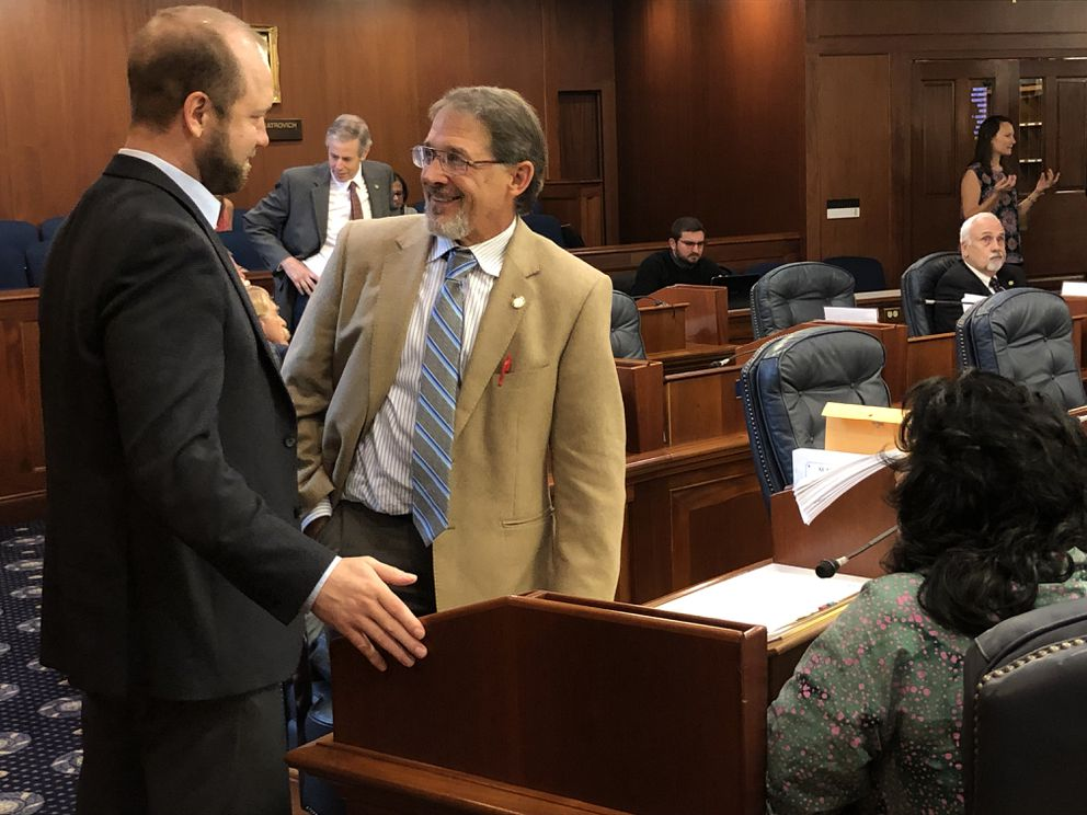 Rep. George Rauscher, R-Sutton, is welcomed back to the Alaska House of Representatives on Friday, July 26, 2019 by Rep. John Lincoln, D-Kotzebue (left). Rauscher has been absent from the House for medical reasons. (James Brooks / ADN)