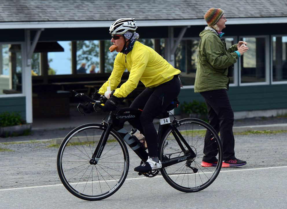 Britta Anderson eats and cycles while departing Seward. (Photo by Erik Hill)