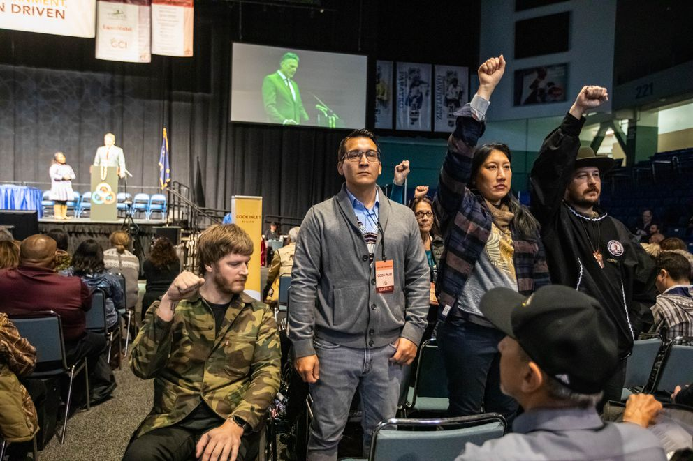 From left, Portugal. The Man guitarist Erik Howk, Kenaitze Tribal Council Treasurer Clinton Lageson, Sedelta Oohsawee, a member of the Cherokee Nation, and Portugal. The Man bassist Zach Carothers stand in silent protest during an address by Gov. Dunleavy at the AFN convention. (Loren Holmes / ADN)