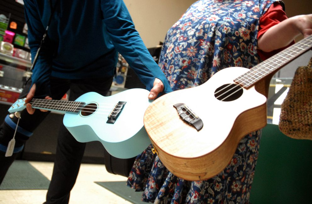 Customers show off their new ukuleles at Mike's Music in Eagle River on Monday, June 3, 2019. The store is closing after 25 years, according to owner Sharon Dunckle. (Matt Tunseth / Chugiak-Eagle River Star)