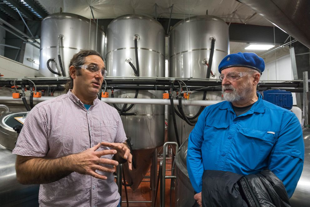 Denali Brewing Co.'s general manager Sassan Mossanen, left, and Mike Kiker, former owner of Celestial Meads who sold his business to Denali Brewingin April, talk at the brewery on Nov. 10. (Loren Holmes / Alaska Dispatch News)