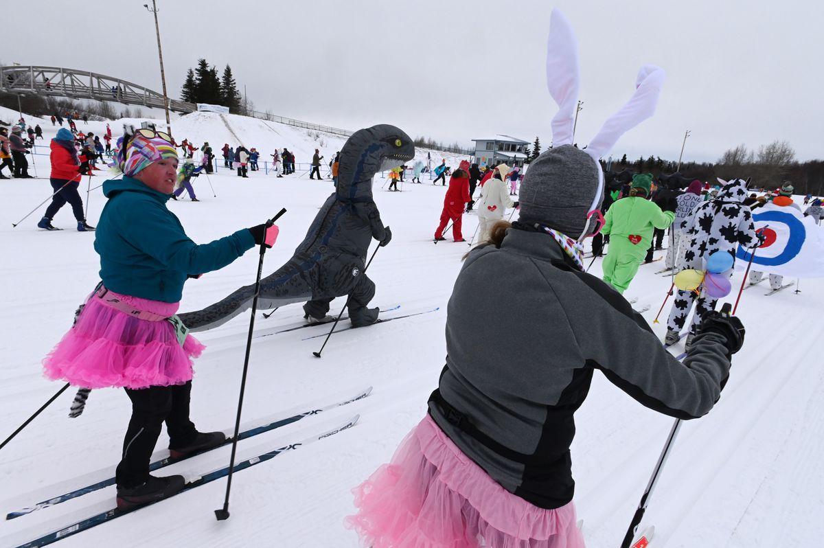 Women in tutus follow a dinosaur out of the Kincaid Park stadium at the 2020 Alaska Ski for Women. (Bill Roth / ADN)