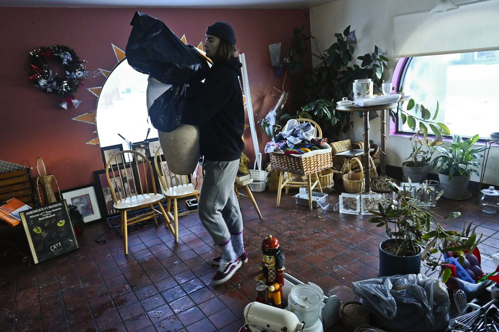Mitchell Newall helps carry items from now-closed Sweet Basil Cafe on Jan. 12. (Marc Lester / ADN)