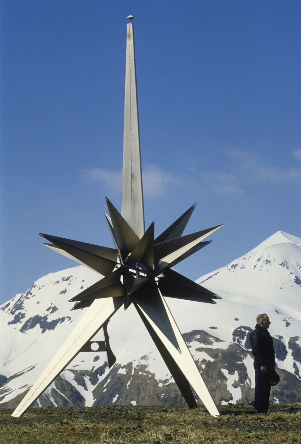 """Fighter pilot John Geddes stands on Attu Island on June 2, 1997, near the monument placed there by the Japanese, five decades after he ditched a Lockheed P-38 """"Lightning"""" into Massacre Bay at Attu after being shot down by a Japanese """"Betty"""" during the Aleutian campaign of World War II. (Bill Roth / ADN archive 1997)"""