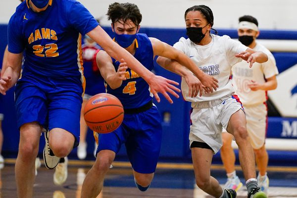 From left, Monroe Catholic's Trevor Mahler, Jase McCullough, and Anchorage Christian's Duey Cook chase a ball during the 3A state championship basketball game on Saturday, March 27, 2021 in Palmer. Monroe won 67-52. (Loren Holmes / ADN)