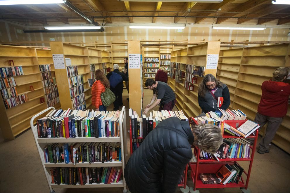 Customers browse books for sale in the warehouse of Title Wave Books on Wednesday, Dec. 5, 2018. The bookstore had about 13,000 books knocked off shelves during the magnitude 7.0 earthquake and is selling them at a discount to minimize the overhead cost of getting them all back in order. (Loren Holmes / ADN)