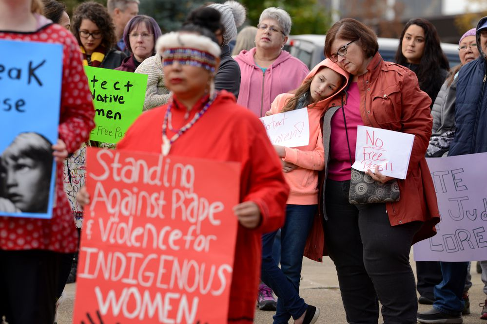 Ada Coyle holds a sign as Ava Robertson leans in to grandaunt Wanetta Ayers at a protest rally in front of the Boney Courthouse in Anchorage, AK on Saturday, Oct 6, 2018. The rally was in protest of Judge Michael Corey who is up for a retention vote in November. (Bob Hallinen / ADN)