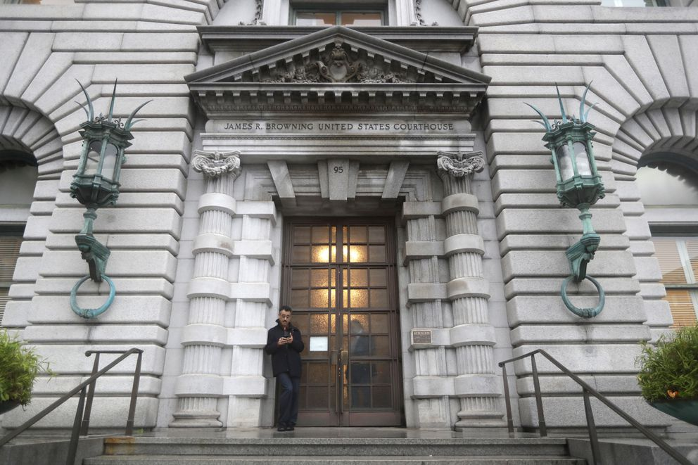 In this Feb. 9, 2017 file photo, a man stands outside the main door outside the 9th U.S. Circuit Court of Appeals building in San Francisco. (AP Photo/Marcio Jose Sanchez, File)