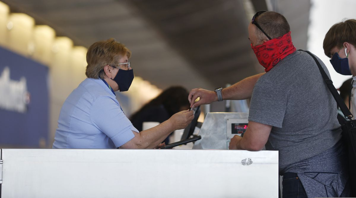 A traveler checks in with an agent at the counter for Alaska Airlines in the main terminal of Denver International Airport late Monday, June 22, 2020, in Denver during the coronavirus pandemic. (AP Photo/David Zalubowski)