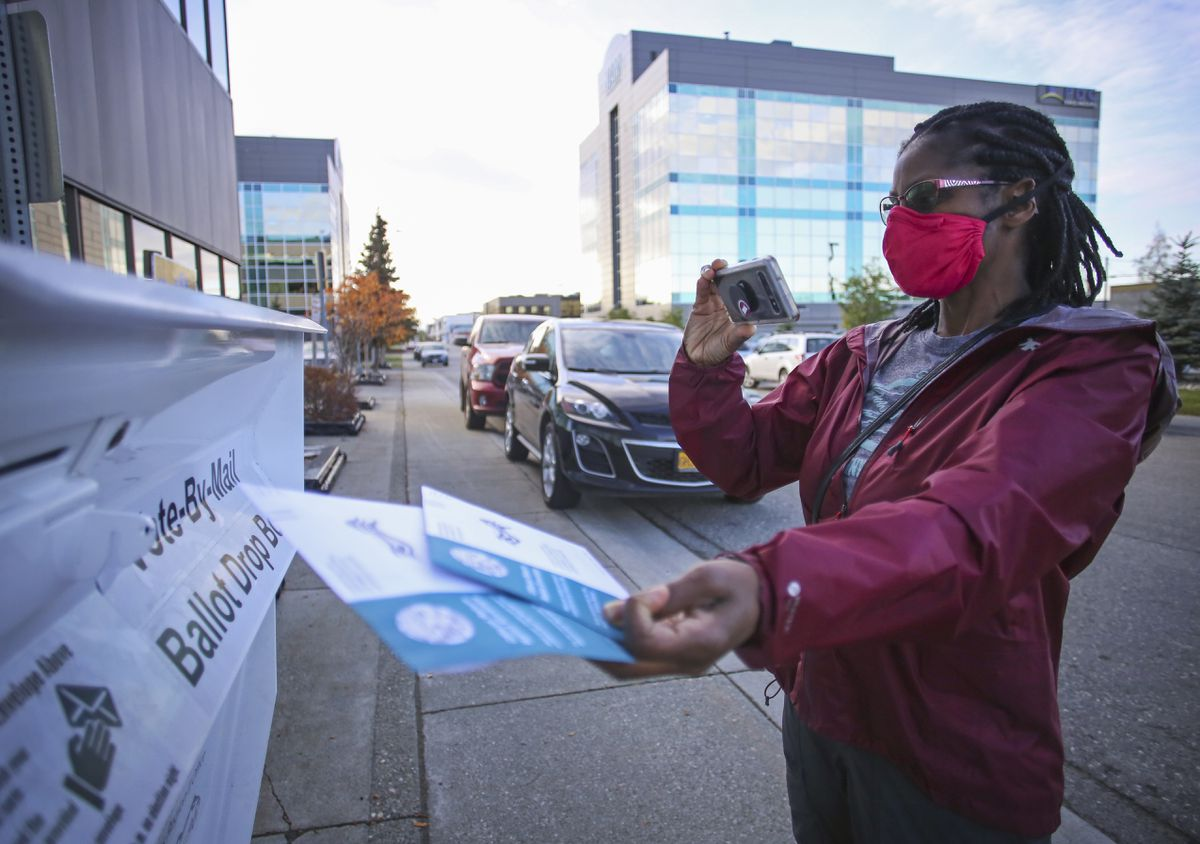 Sheri Boggs takes a photo with her completed 2020 general election ballot before placing it in the dropbox outside the State Division of Elections office, located at 2525 Gambell St., in Anchorage on Oct. 13, 2020. (Emily Mesner / ADN)
