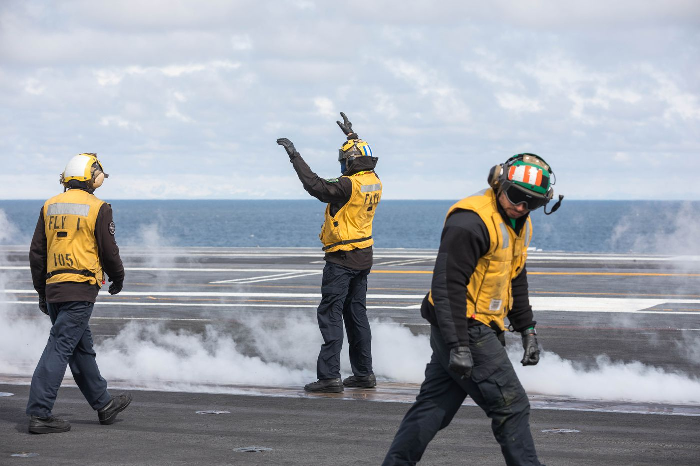 Flight deck personnel prepare for an aircraft launch on Wednesday aboard the USS Theodore Roosevelt Nimitz-class aircraft carrier in the Gulf of Alaska south of Seward. Flight deck personnel wear color-coded shirts that correspond to their job. Yellow shirts are tasked with directing planes, managing the catapult and arresting cables, and handling aircraft while they are on deck. (Loren Holmes / ADN)