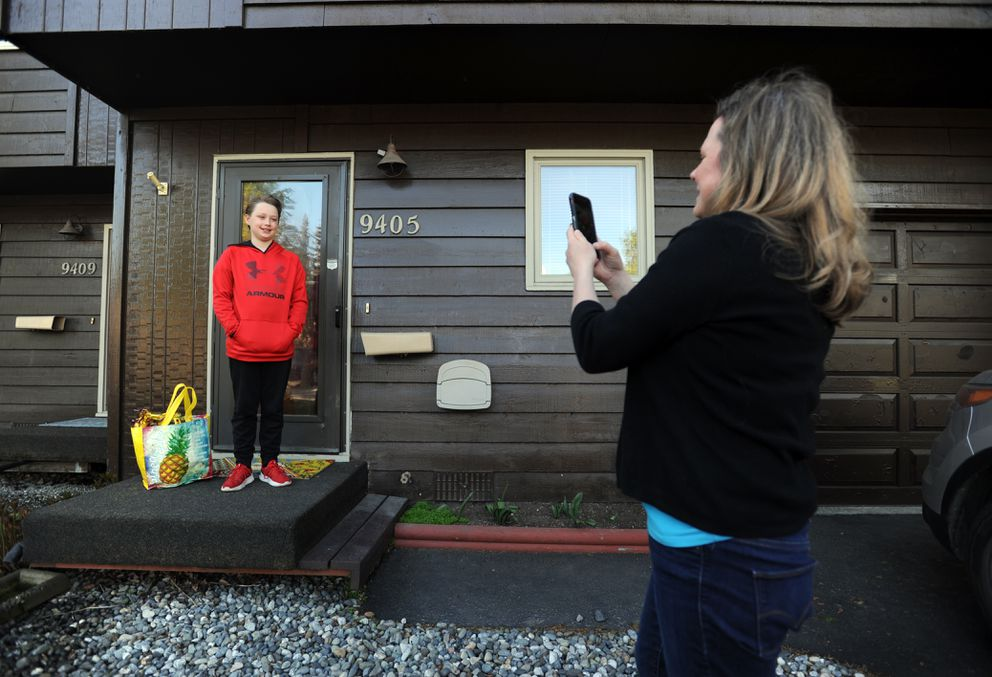 Lisa Heikes, right, photographs Kohl Russell as they leave their house for Kohl's last day of elementary school on Tuesday morning May 22, 2019, in south Anchorage. (Erik Hill)