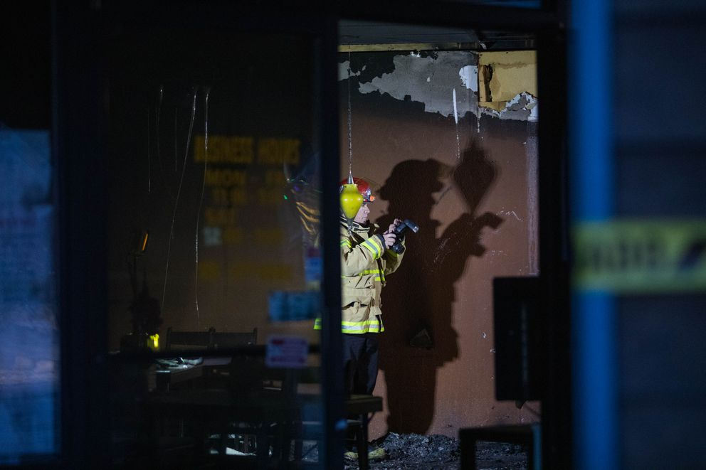 Anchorage fire investigator Brian Dean works the scene of a fire at Noodle World on Thursday morning. Noodle World is in the same building as Yakitori Sushi House, which burned Monday morning under circumstances that police describe as arson. (Loren Holmes / ADN)