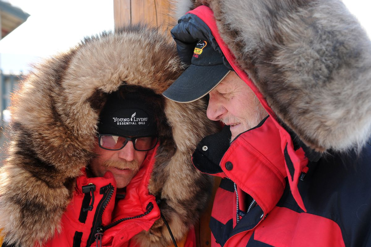 Iditarod musher Mitch Seavey talks with his father, Dan Seavey, as they wait for Mitch's son, Dallas, to finish the Iditarod Trail Sled Dog Race on Tuesday. Mitch won his third Iditarod this year, Dallas came in second. Dan has raced five Iditarods, including the first ever in 1973. (Bob Hallinen / Alaska Dispatch News)