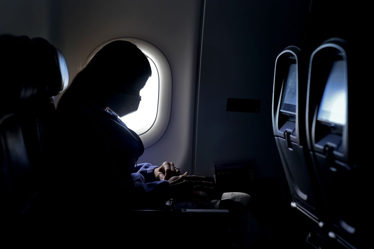 A passenger wears a face mask she travels on a Delta Airlines flight Wednesday, Feb. 3, 2021, after taking off from Hartsfield-Jackson International Airport in Atlanta. (AP Photo/Charlie Riedel)