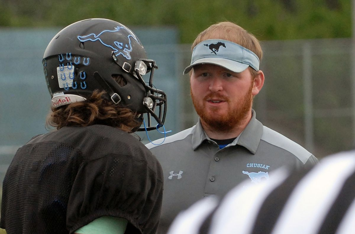 Chugiak assistant football coach Kody Trombley speaks to a player at practice earlier this fall. Trombley, a 2012 Chugiak grad who attended the University of Central Florida, recently became the school's new band director. He's one of two former Mirror Lake Middle School band students to take over an ASD band program this fall; Jonathan Cannamore, an Eagle River High grad, is the other. (Star photo by Matt Tunseth)
