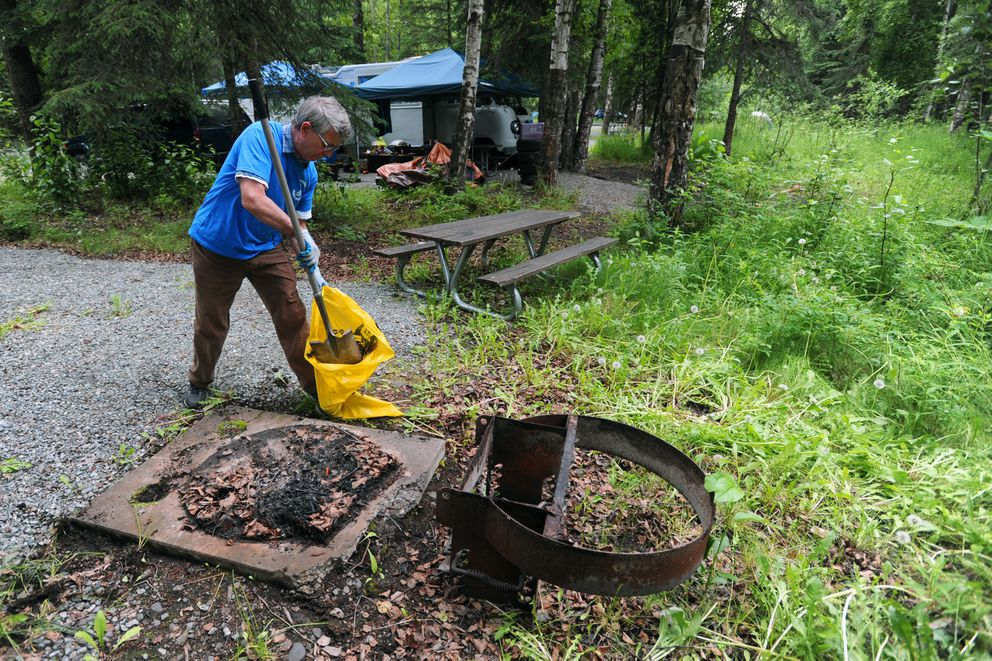 Jerry Paliwoda cleans out a fire pit while inspecting vacant camp sites on Wednesday at Centennial Park Campground. He said staffers are vigilant about maintaining clean sites for customers, which also helps avoid attracting wildlife. (Erik Hill / Alaska Dispatch News)