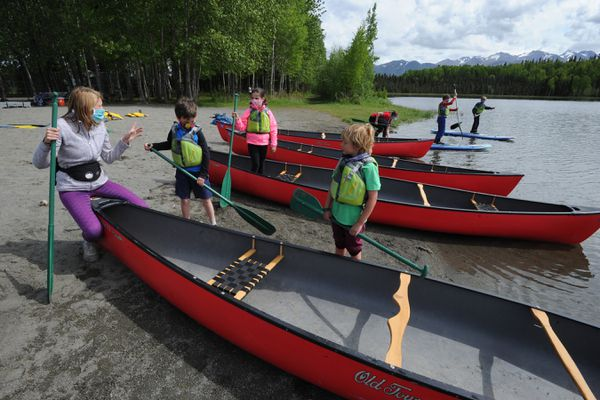 Trailside Discovery Camp program manager Acadia Graham, left, helps launch canoes at Goose Lake in Anchorage on Monday, June 1, 2020. (Bill Roth / ADN)