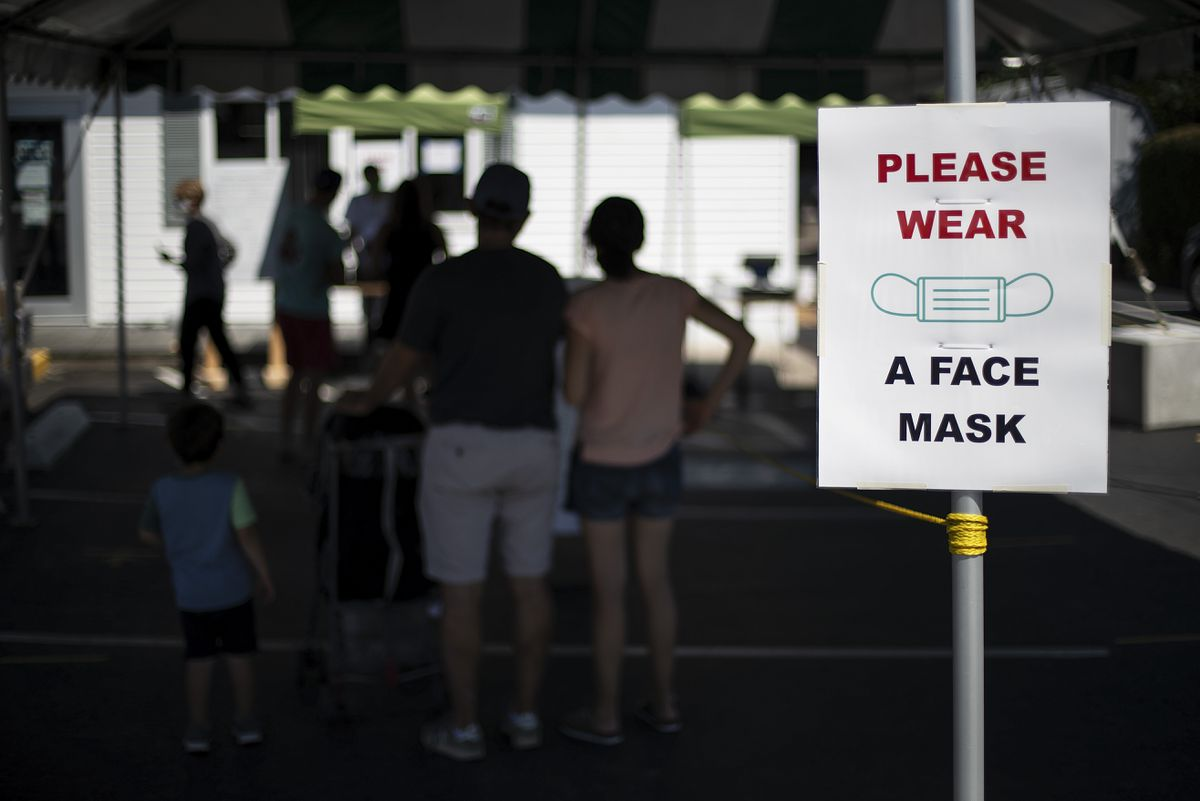 Customers with masks line up at a Brickley's Ice Cream shop in Narragansett, R.I., Wednesday, July 29, 2020. (AP Photo/David Goldman)