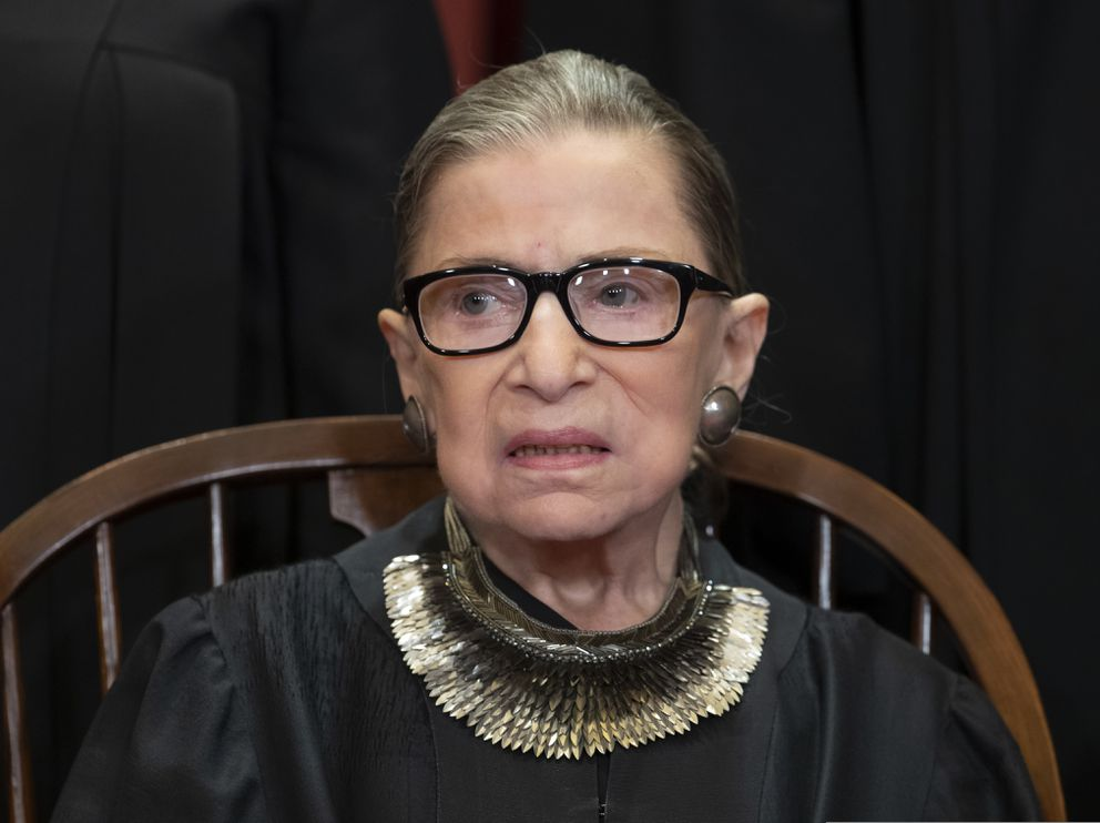 FILE - In this Nov. 30, 2018 file photo, Associate Justice Ruth Bader Ginsburg sits with fellow Supreme Court justices for a group portrait at the Supreme Court Building in Washington. Ginsburg has missed a month of Supreme Court arguments as she recovers from lung cancer surgery. But she's not the first justice to be away for a while and her absence hardly compares with those of some of her predecessors. (AP Photo/J. Scott Applewhite)