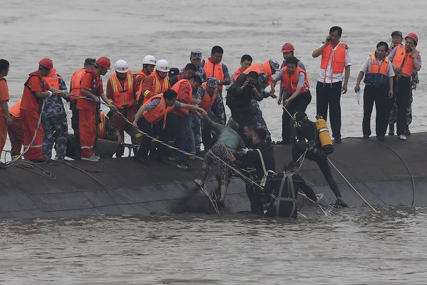 In this photo released by China's Xinhua News Agency, rescuers save a survivor, center, from the overturned passenger ship in the Jianli section of the Yangtze River in central China's Hubei Province Tuesday, June 2, 2015. Rescuers pulled several survivors to safety after hearing cries for help Tuesday from inside a capsized cruise ship that went down overnight in a storm on China's Yangtze River, state broadcaster CCTV said.