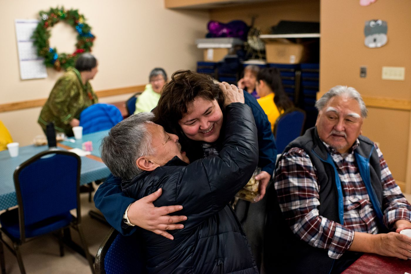 """Arnold Brower gets a hug from Susan Hope during a holiday dinner at the North Slope Borough Senior Center. Brower says he's open to the city's name change as it was approved by voters, and that people will accept it in time. """"I know it won by a small margin but that's what politics is,"""" he said. (Marc Lester / Alaska Dispatch News)"""