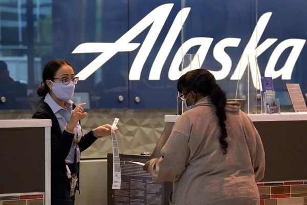 A gate agent with Alaska Airlines assist a traveler at the ticketing counter at Love Field Airport in Dallas, Tuesday, Nov. 24, 2020. (AP Photo/Tony Gutierrez)