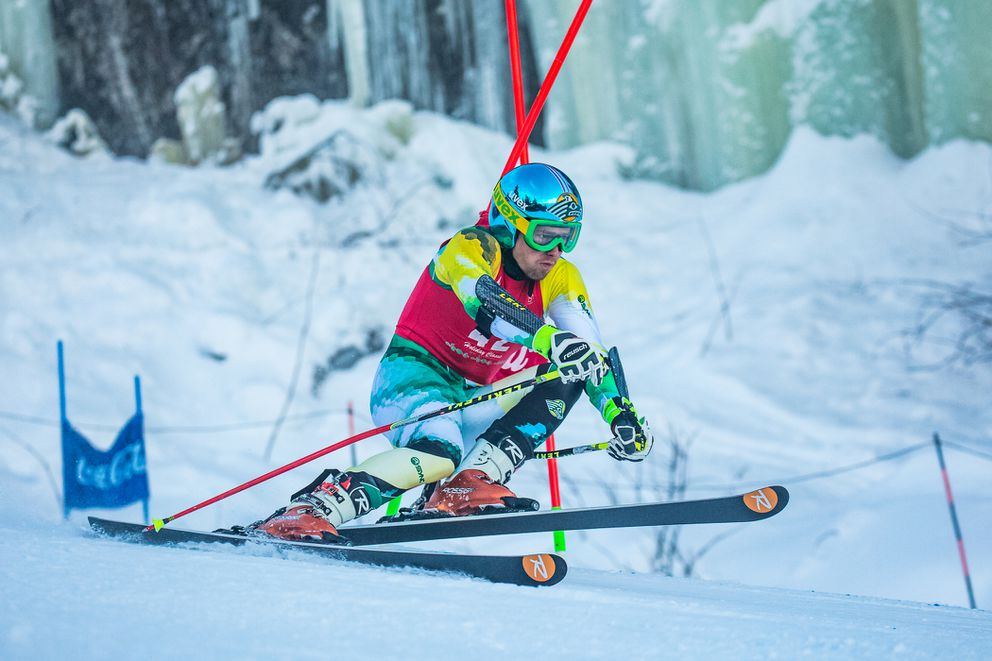 Framed by icefalls near Alyeska's Steilhung, UAA racer Martins Onskulis rips through a gate in the first of two Coca-Cola Holiday Classic giant slaloms Monday. (Photo by Bob Eastaugh)