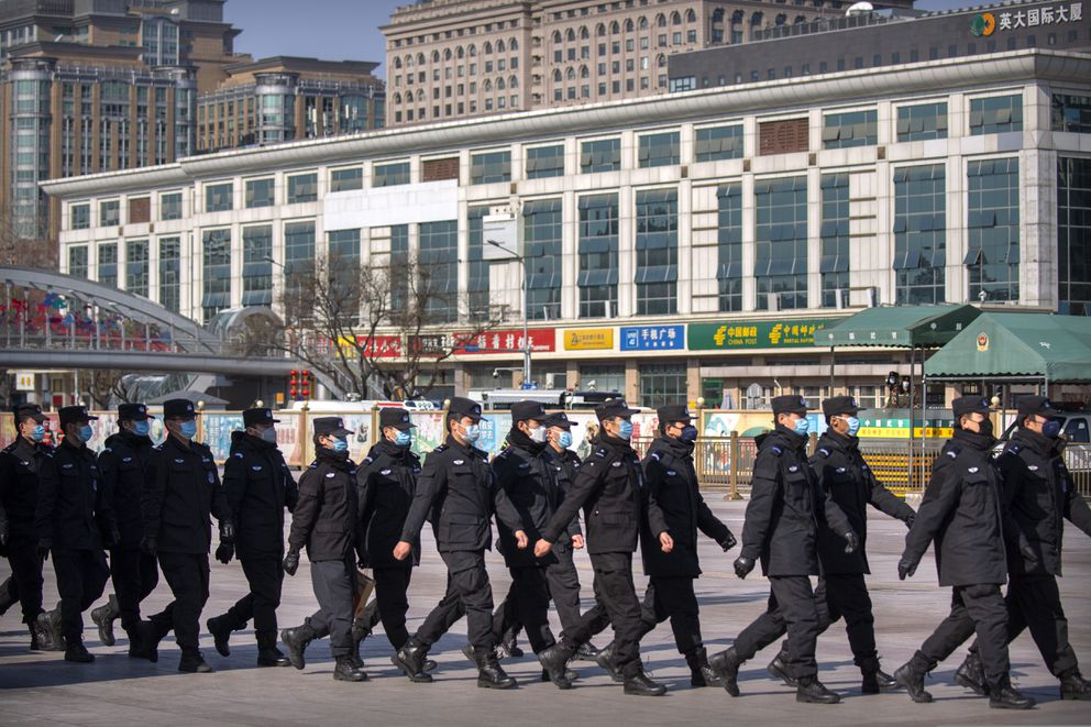 Policemen wear face masks as they march in formation outside the Beijing Railway Station in Beijing, Saturday, Feb. 15, 2020. (AP Photo/Mark Schiefelbein)