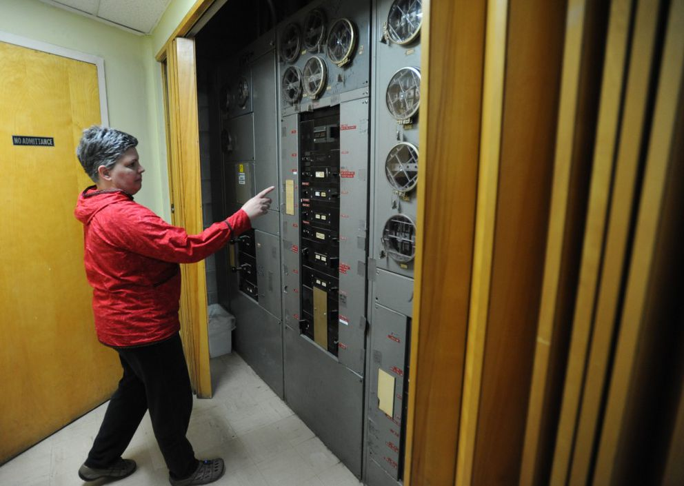 Facility manager Angela Taplin points out the aging electrical panel in the basement of the Arne Beltz Building on Tuesday, May 3, 2016, that is home to the Anchorage Department of Health and Human Services. (Bill Roth / ADN)