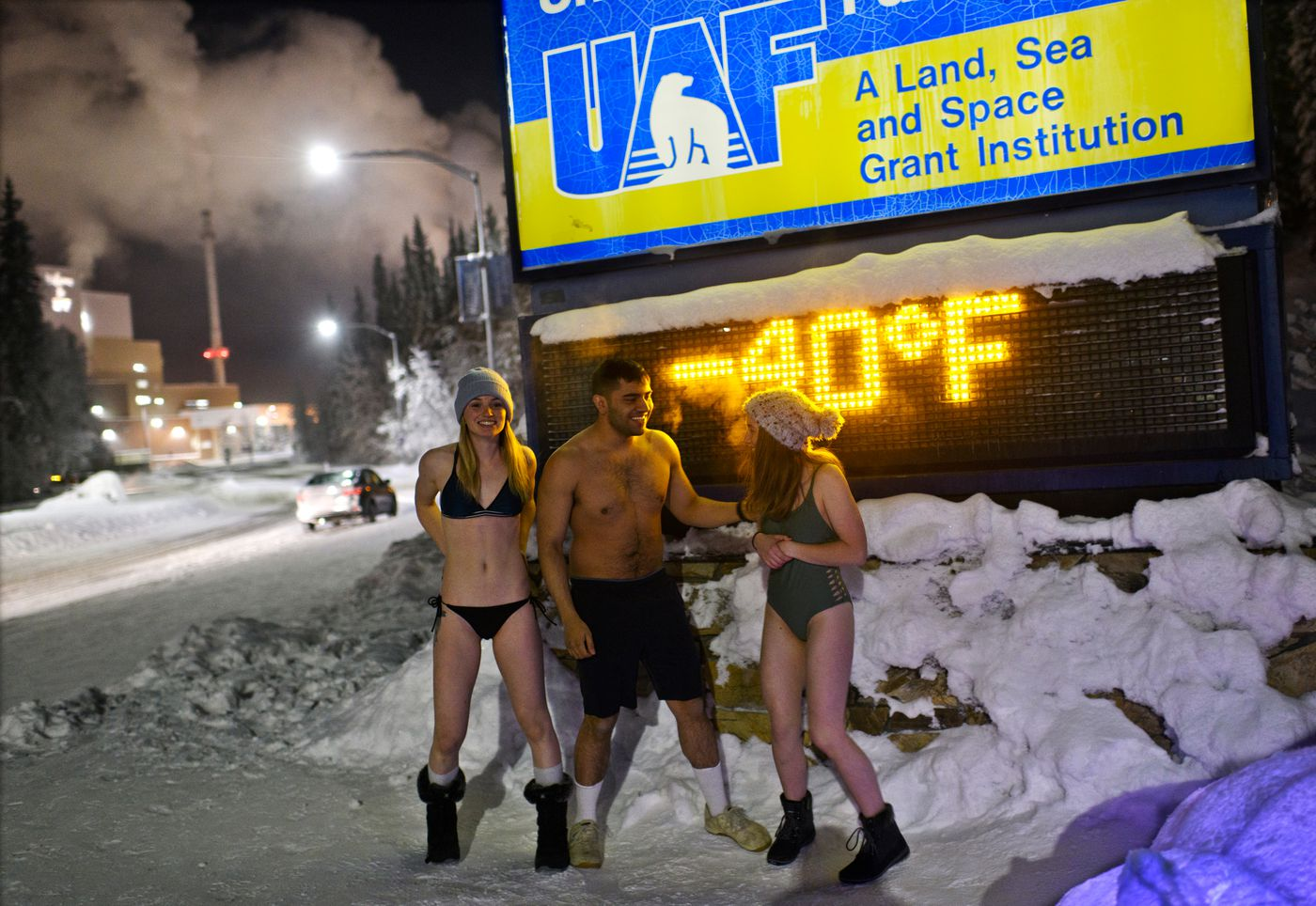 From left, Lauren Pinto, Bruce Sandoval and Camryn Sandoval gather for a photo in front of a minus-40-degree temperature reading at UAF. (Marc Lester / ADN)