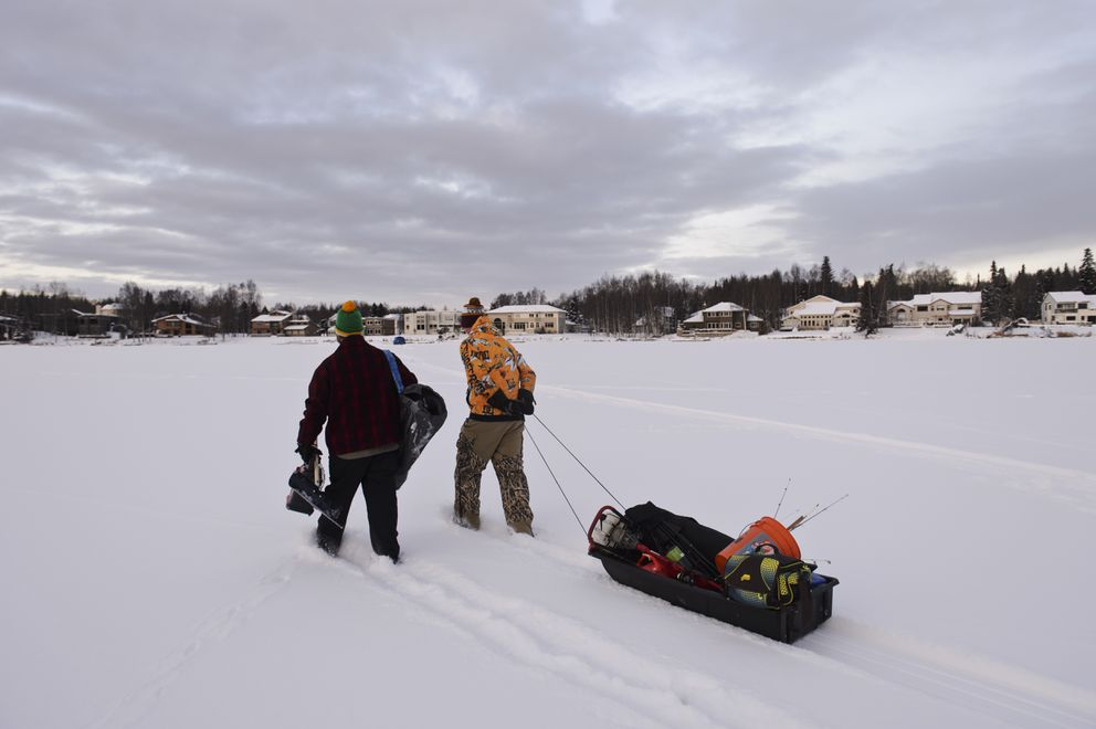 Matthew Driskell, left, and Taylor Baker pull their ice fishing gear in a sled across the snow on Sand Lake. (Marc Lester / ADN)
