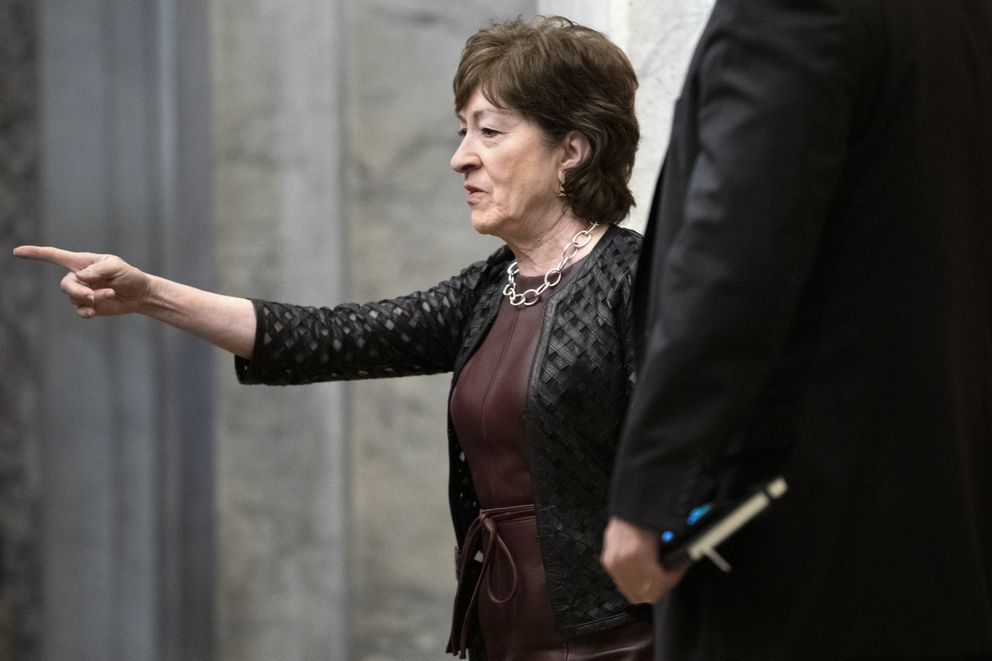Sen. Susan Collins, R-Maine, points toward the elevator as she arrives, Wednesday, Jan. 29, 2020, on Capitol Hill in Washington, for the impeachment trial of President Donald Trump on charges of abuse of power and obstruction of Congress. (AP Photo/ Jacquelyn Martin)