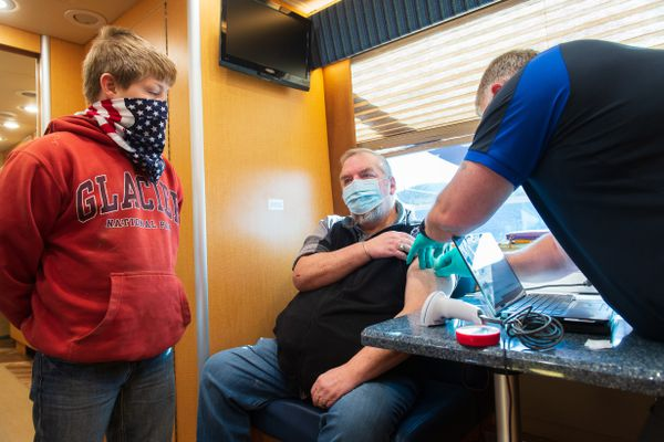 Logan, 11, and his father, U.S. Air Force veteran Mike Jellesed, 61 of Libby, Mont., after a long discussion, receives the Moderna Vaccine from RN Mark Sheldon on March 30, 2021. (Photo by Tony Bynum for The Washington Post)