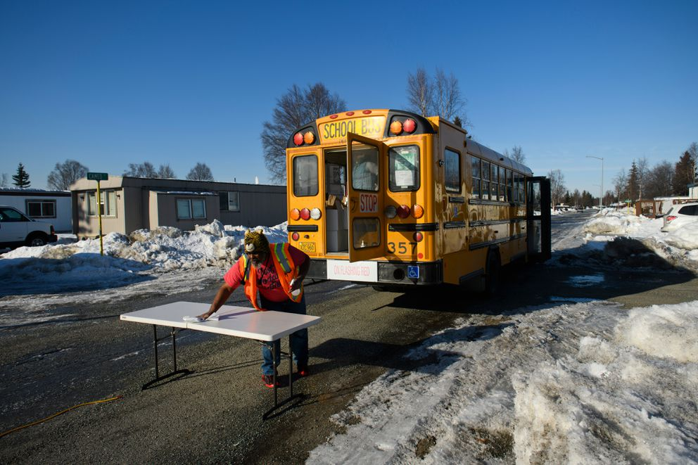 Leonard Collins, a bus driving instructor for Reliant Transportation, cleans a table before delivering lunches in South Anchorage. (Marc Lester / ADN)
