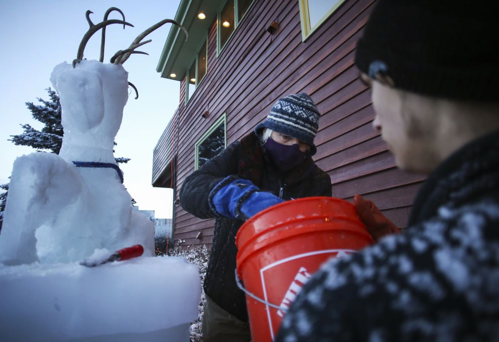 Jimmie Froehlich grabs slush from a bucket held by Trace Edmundson while they work on completing a Christmas ice sculpture. (Emily Mesner / ADN)