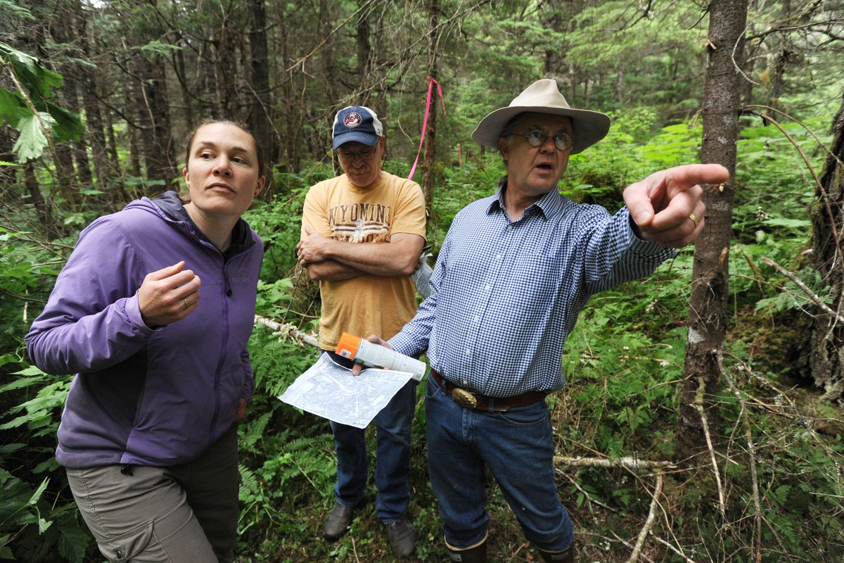 Tommy O'Malley, right, points out a boundary line during an open house to familiarize the Girdwood community with the location of the proposed cemetery site on Sunday. (Bill Roth / Alaska Dispatch News)
